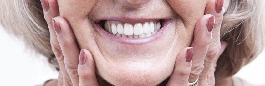 A woman smiling and shower her dentures