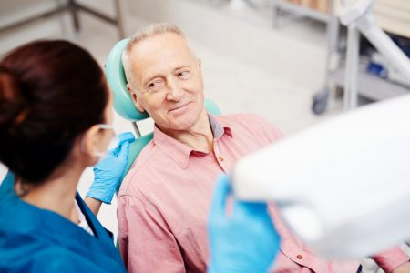man looks at his dentist before his denture appointment